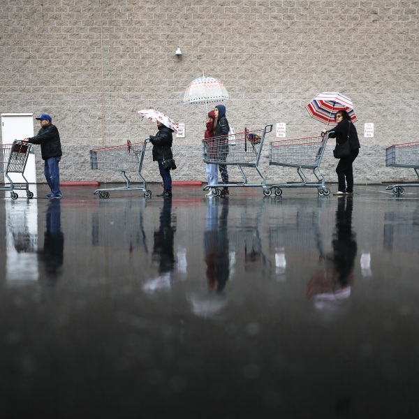 Shoppers wait in line in the rain to enter a Costco Wholesale store on March 14, 2020 in Glendale. (Mario Tama/Getty Images)