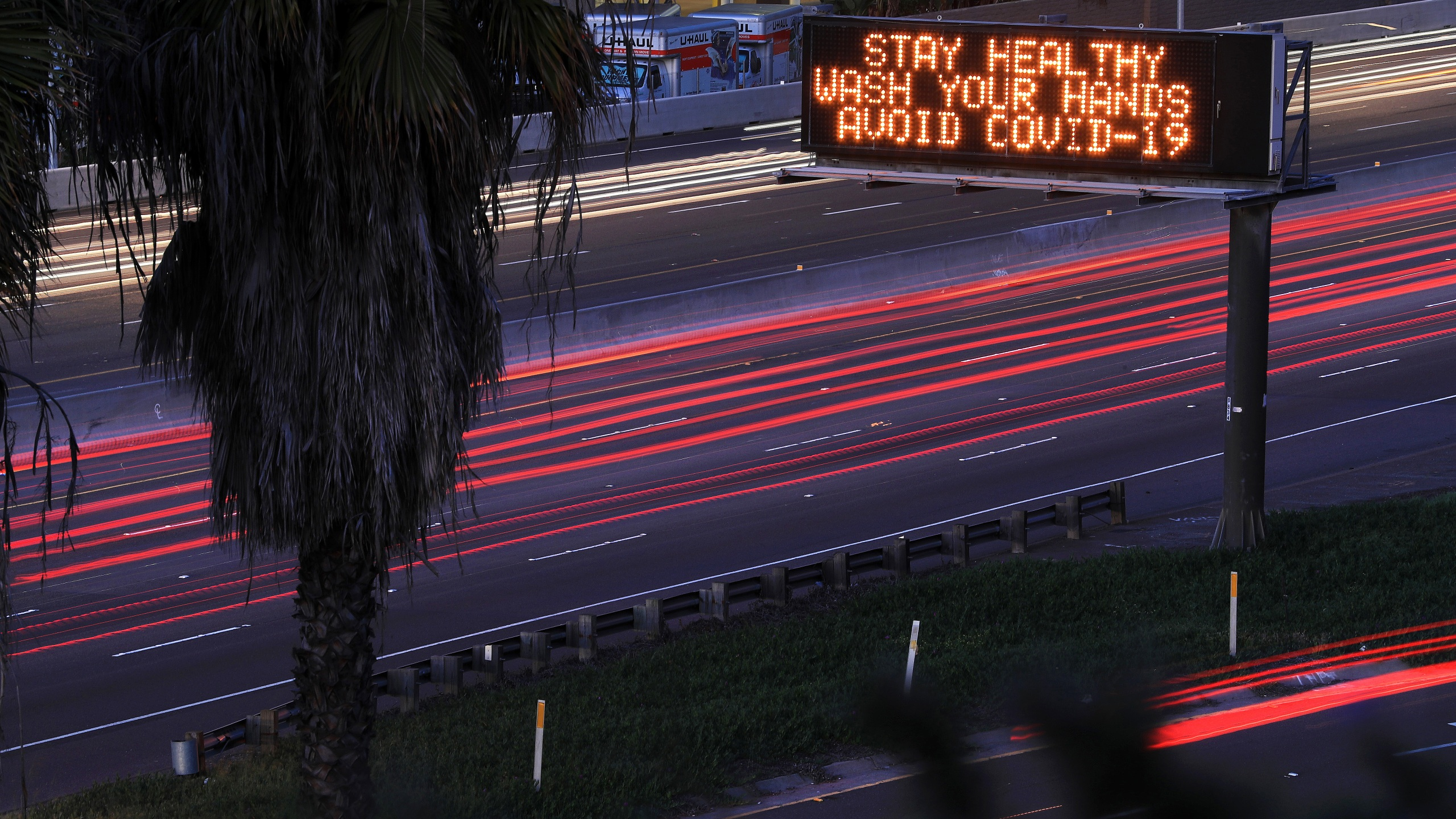 Motorists travel on Interstate 8 in San Diego as a sign encourages hand washing on March 15, 2020. (Credit: Sean M. Haffey / Getty Images)