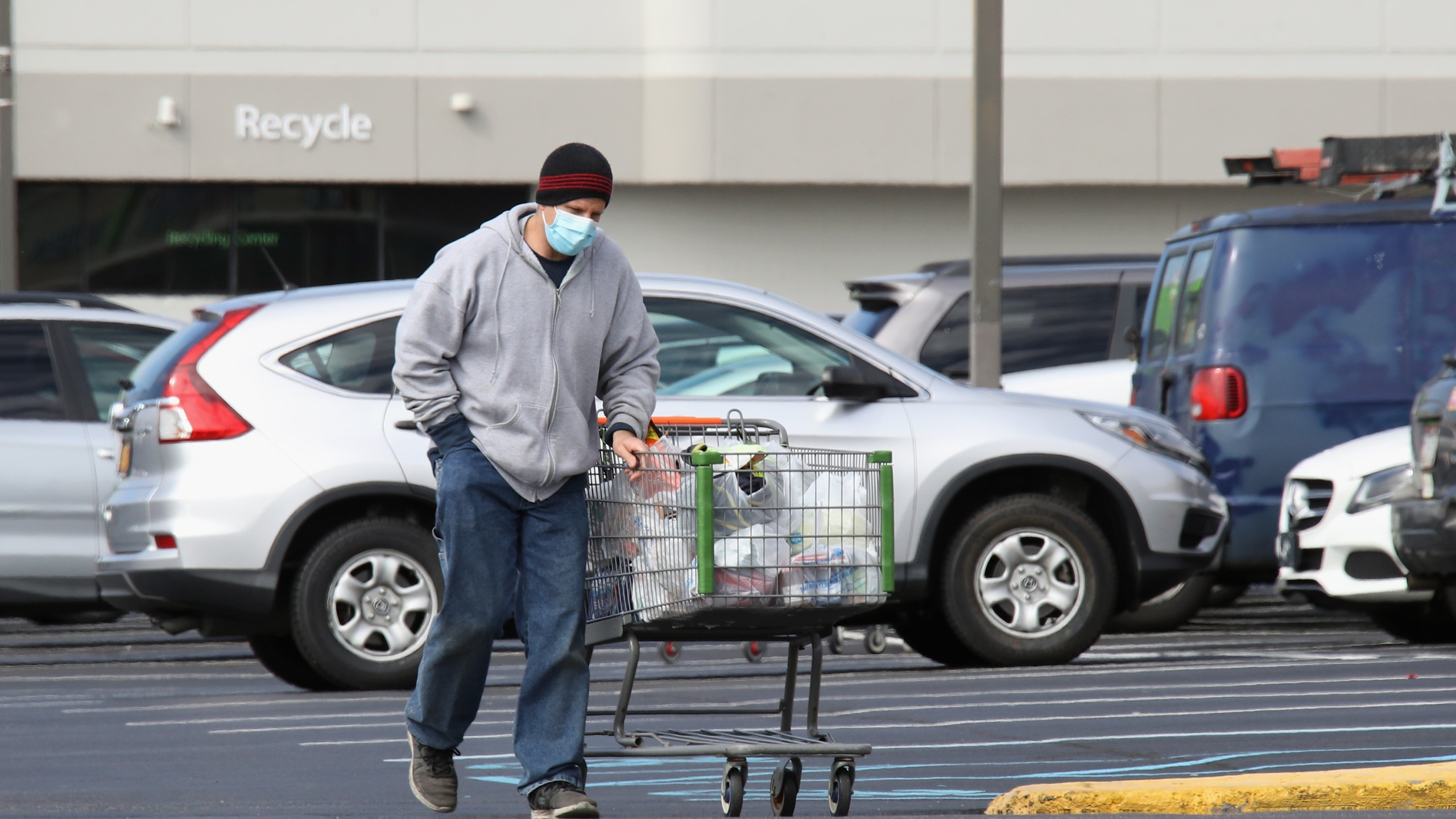 A shopper wearing a face mask returns to his car with goods from a Walmart Neighborhood Market as the coronavirus continues to spread across the United States on March 16, 2020 in Levittown, New York. (Bruce Bennett/Getty Images)