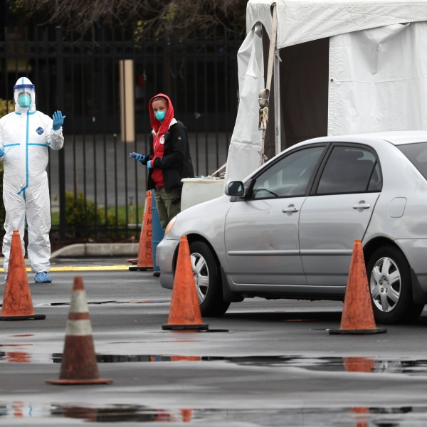 A medical worker guides a car that is going through a coronavirus drive-thru test clinic at the San Mateo County Event Center on March 16, 2020 in San Mateo, California. (Justin Sullivan/Getty Images)