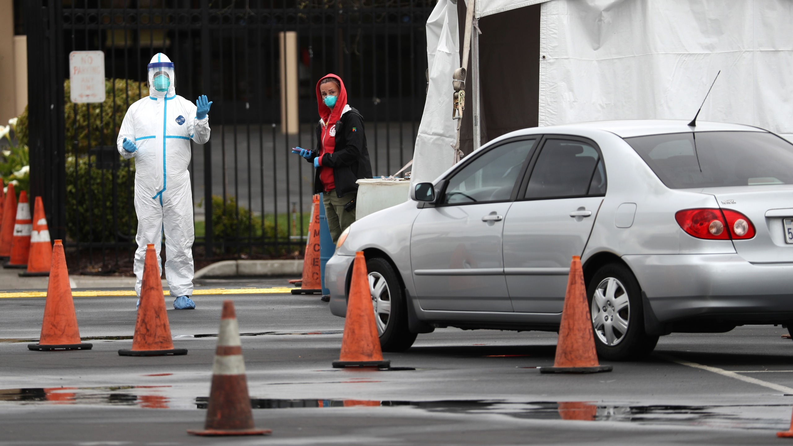 A medical worker guides a car that is going through a coronavirus drive-thru test clinic at the San Mateo County Event Center on March 16, 2020, in San Mateo, California. (Justin Sullivan/Getty Images)