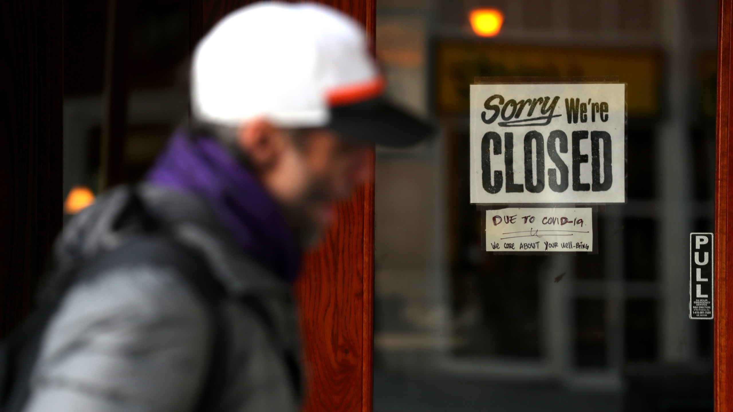 A pedestrian walks by a closed sign on the door of a restaurant in San Francisco on March 17, 2020. (Justin Sullivan / Getty Images)