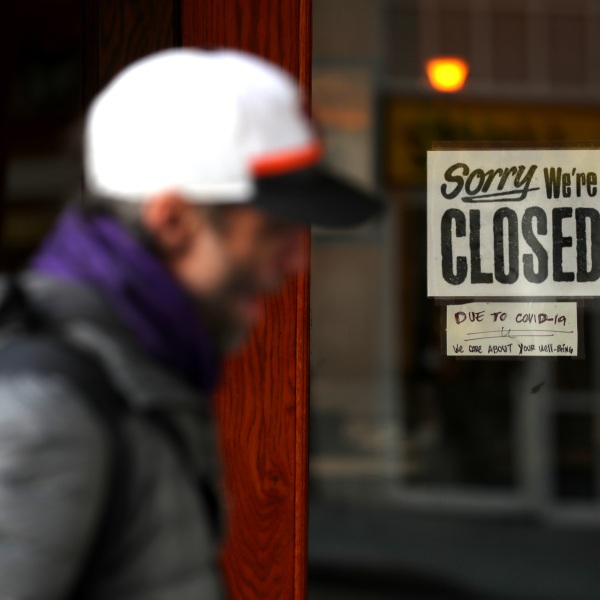 A pedestrian walks by a closed sign on the door of a restaurant on March 17, 2020 in San Francisco, California. (Justin Sullivan/Getty Images)
