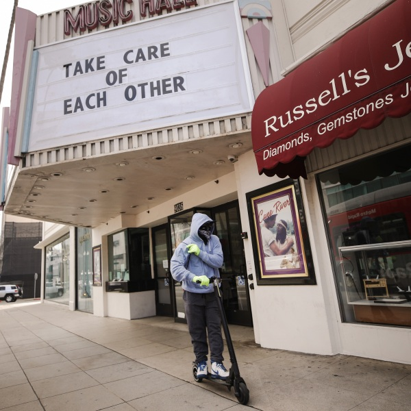 """A man wears gloves and a bandanna across his face while riding a scooter past a shuttered movie theater with the message """"take care of each other"""" displayed on the marquee in Beverly Hills on March 18, 2020. (Credit: Mario Tama / Getty Images)"""