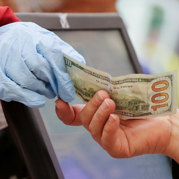 A woman pays cash while wearing gloves during special hours open only to seniors and the disabled at a Northgate market on March 19, 2020 in Los Angeles. (Credit: Mario Tama/Getty Images)