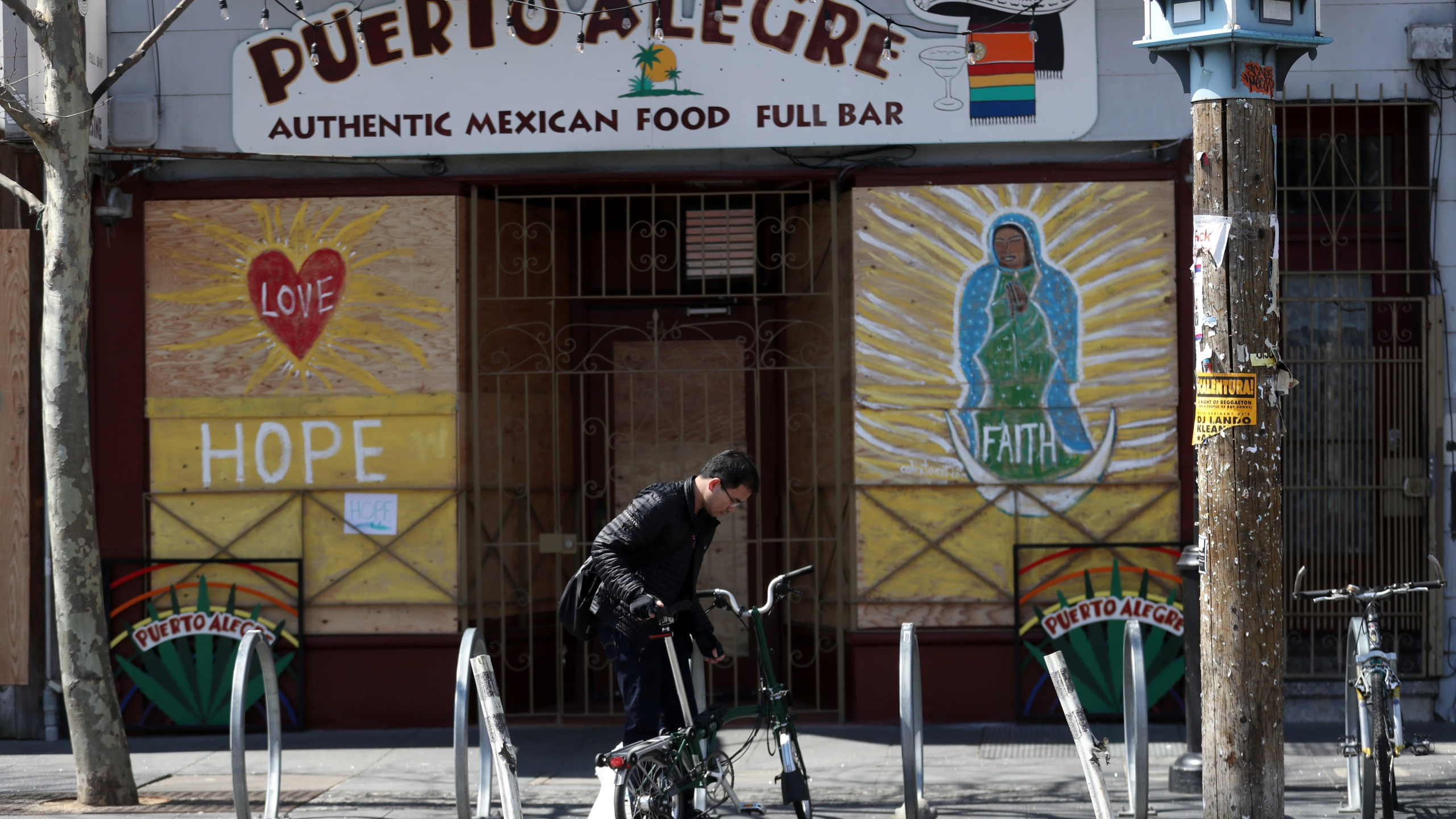 A cyclist parks his bicycle in front of a business that has the windows covered with plywood on Valencia Street on March 20, 2020 in San Francisco. (Justin Sullivan/Getty Images)