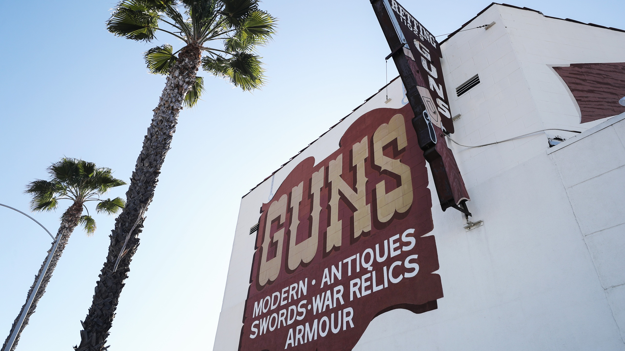 Palm trees stand next to the Martin B. Retting, Inc. guns store as the coronavirus pandemic continues on March 24, 2020, in Culver City. (Mario Tama/Getty Images)