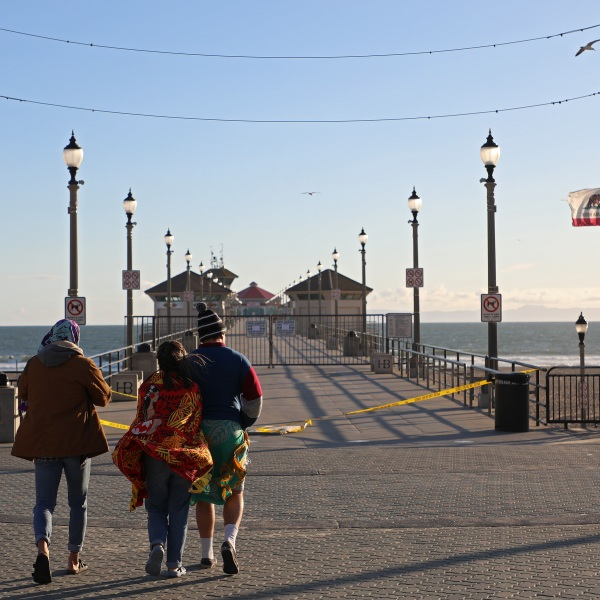 People stand in front of the closed Huntington Beach Pier on March 24, 2020. (Credit: Michael Heiman / Getty Images)