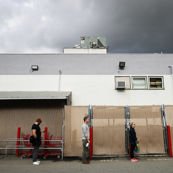 People maintain social distancing while standing in line to enter a Trader Joe's as the coronavirus pandemic continues on March 25, 2020, in Los Angeles. (Mario Tama/Getty Images)