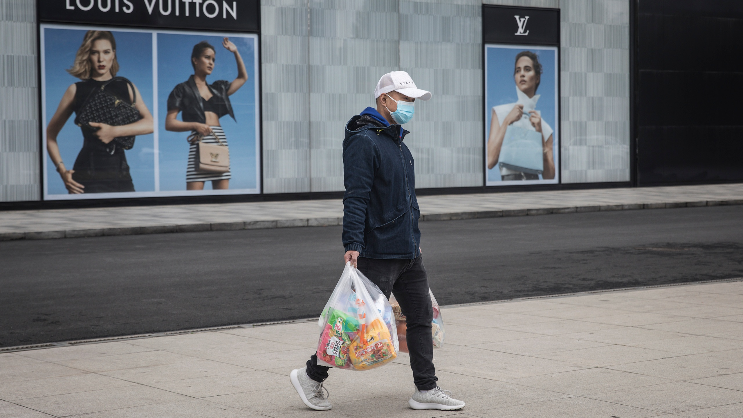 A man wearing a face mask passes a Louis Vuitton store outside Wuhan international plaza on March 30, 2020, in Hubei Province, China. (Getty Images)
