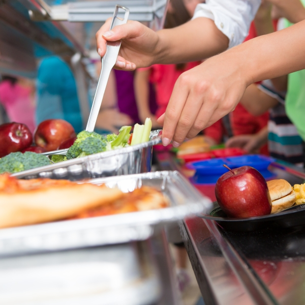 A cafeteria worker helps elementary students select food in a lunch line (Getty Images)
