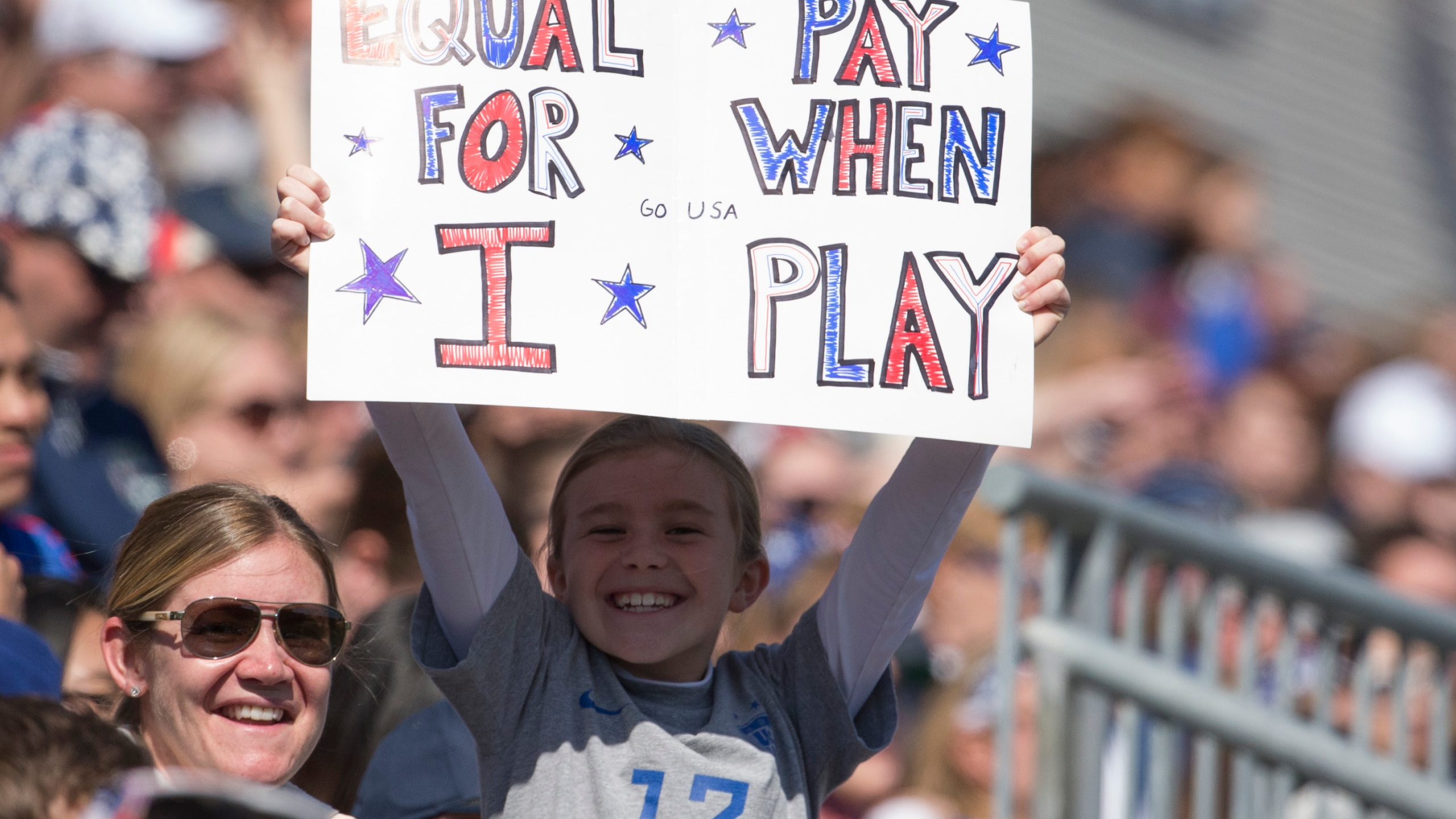 "A fan of the United States holds a sign that reads, ""Equal pay for when I play"" during the game against Colombia at Talen Energy Stadium on April 10, 2016, in Chester, Pennsylvania. (Mitchell Leff/Getty Images)"