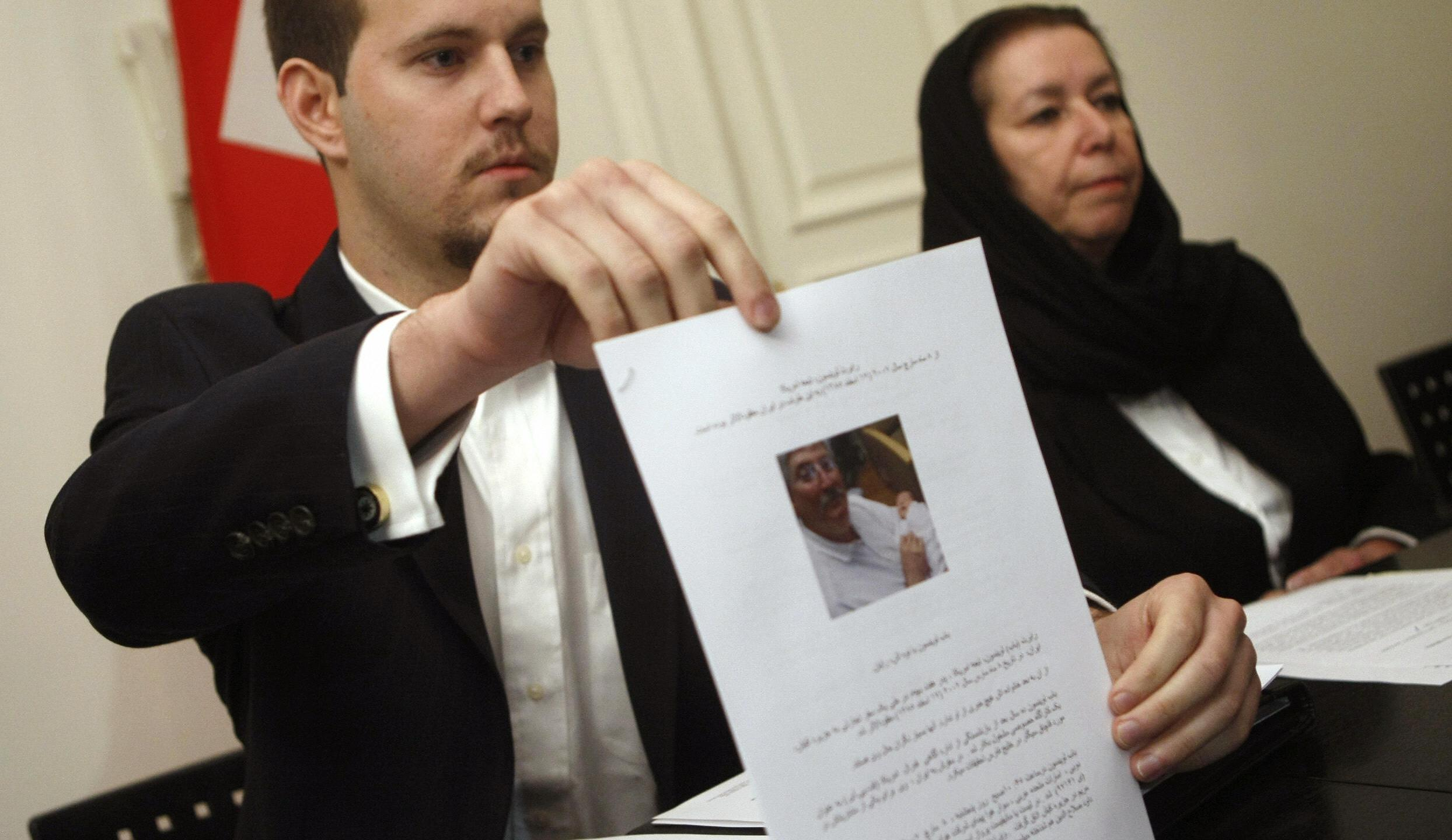 Daniel Levinson (left) shows a picture of his father, ex-FBI agent Robert Levinson, holding his grandson Ryan during a press conference with his mother Christine at the Swiss embassy in Tehran on Dec. 22 2007. (BEHROUZ MEHRI/AFP via Getty Images)