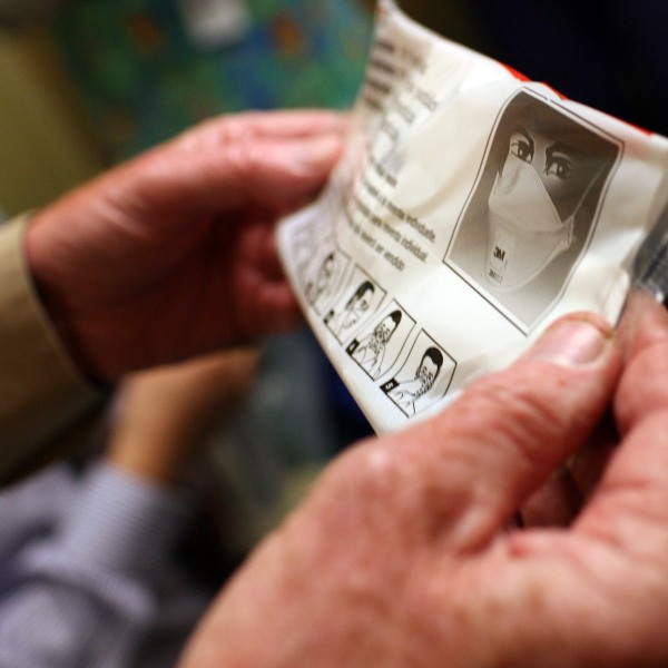 A hospital worker holds up the instructions for using an N95 respiratory mask in a file photo. (Justin Sullivan/Getty Images)