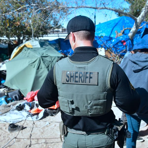 A deputy walks through a homeless encampment beside the Santa Ana River in Anaheim on Feb. 20, 2018.(Frederic J. Brown/ AFP via Getty Images)