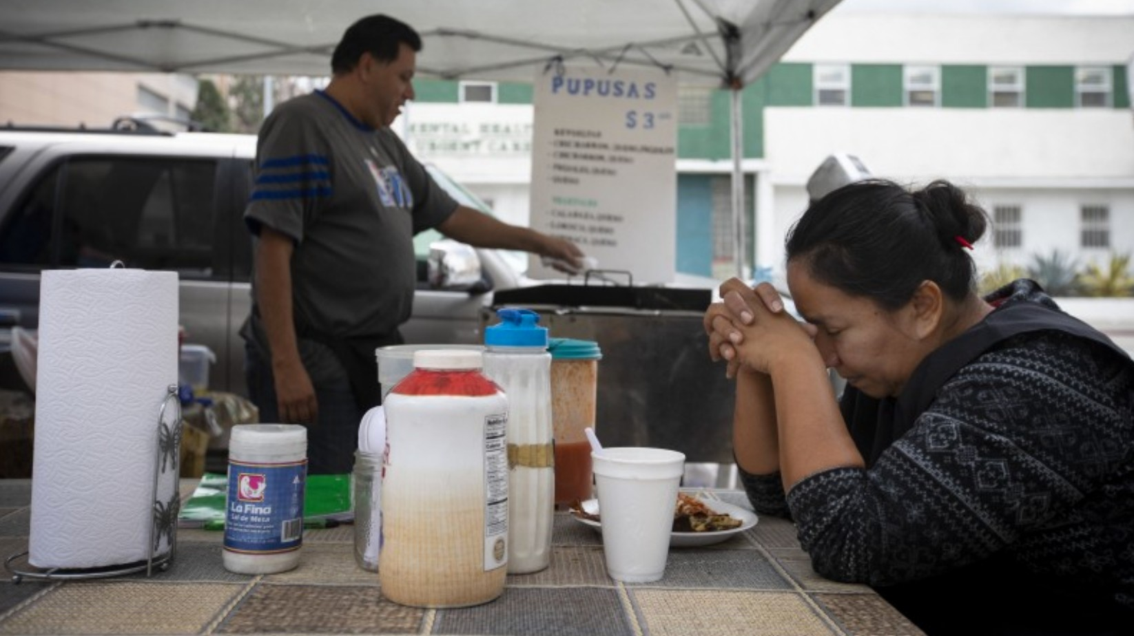 Patricia Escobar prays before having her lunch she bought from a vendor outside County-USC Medical Center on March 17, 2020. (Francine Orr/Los Angeles Times)