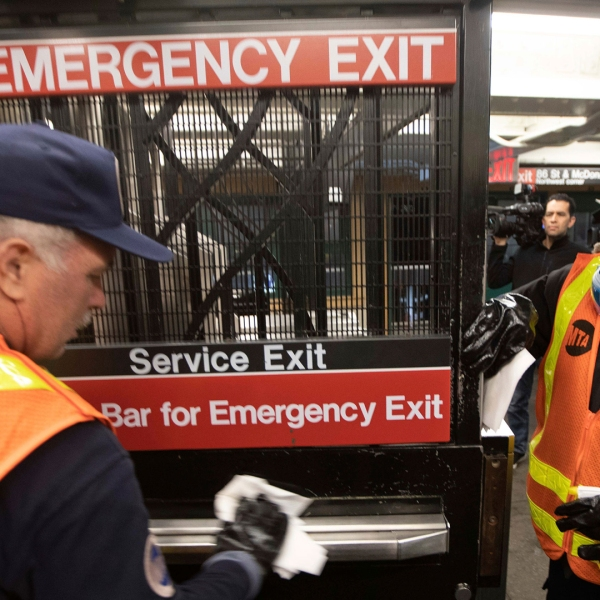 Metropolitan Transportation Authority workers Duane Clark, left, and S. Williams work to sanitize surfaces at the Avenue X subway station, Tuesday, March 3, 2020, in the Brooklyn borough of New York. The MTA is stepping up efforts to sanitize cars and stations as fears mount over the coronavirus. (AP Photo/Kevin Hagen)