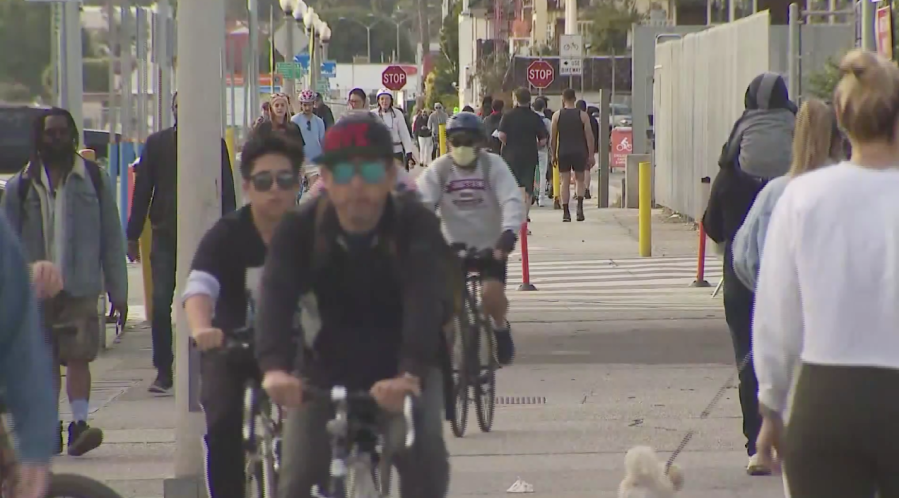 People ride bikes on the Santa Monica Pier on March 22, 2020. (KTLA)