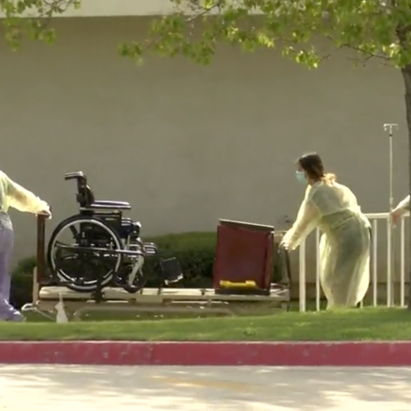 Staff is seen bringing out wheelchairs and beds from the Cedar Mountain Post Acute nursing home in Yucaipa after one death and 12 COVID-19 cases were confirmed on March 28, 2020. (Inland News)