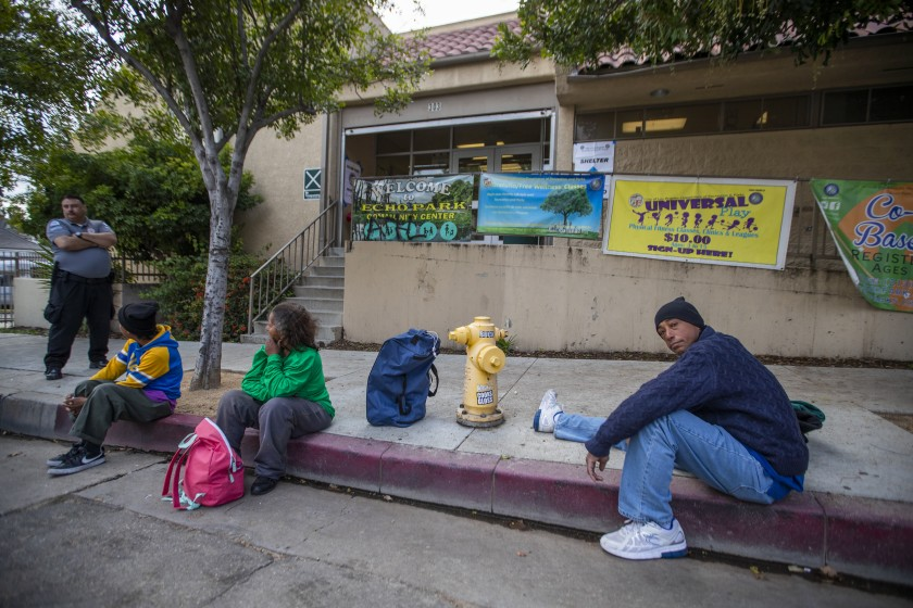 Tyrone Dixon, right, arrives with other people who are homeless at the Echo Park Community Center, one of several recreation centers being converted to shelters, on March 20, 2020. (Allen J. Schaben / Los Angeles Times)