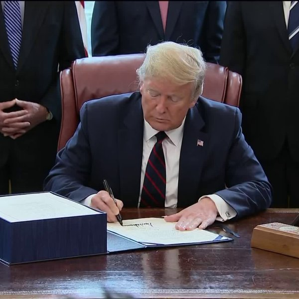 President Donald Trump signs a $2.2 trillion stimulus package to aid in COVID-19 recovery on March 27, 2020.