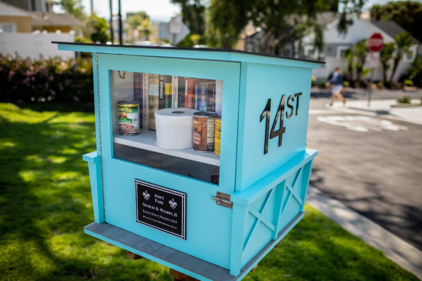 A lending library included some additional useful items, including a roll of toilet paper and cans of beans and corn, in a Hermosa Beach neighborhood on Sunday.(Jay L. Clendenin / Los Angeles Times)