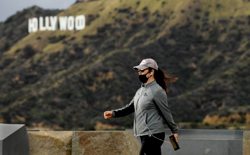 A hiker wears a mask during a walk past the Hollywood sign in Griffith Park on March 23, 2020.(Wally Skalij / Los Angeles Times)