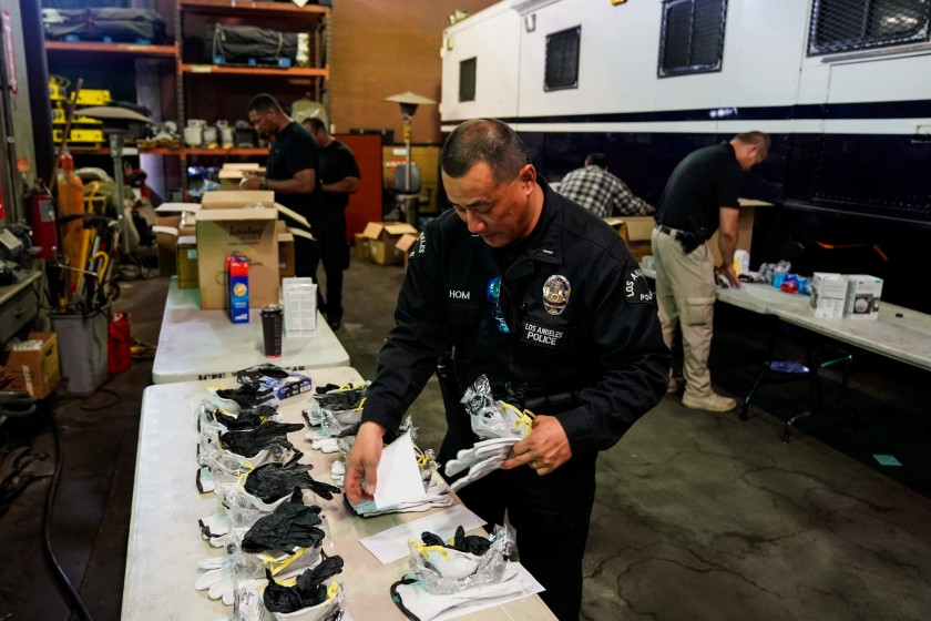 In March 2020, LAPD Lt. Jay Hom helps assemble kits consisting of an N95 mask, work gloves and nitrile gloves for field officers to protect themselves from exposure to the coronavirus. (Kent Nishimura / Los Angeles Times)