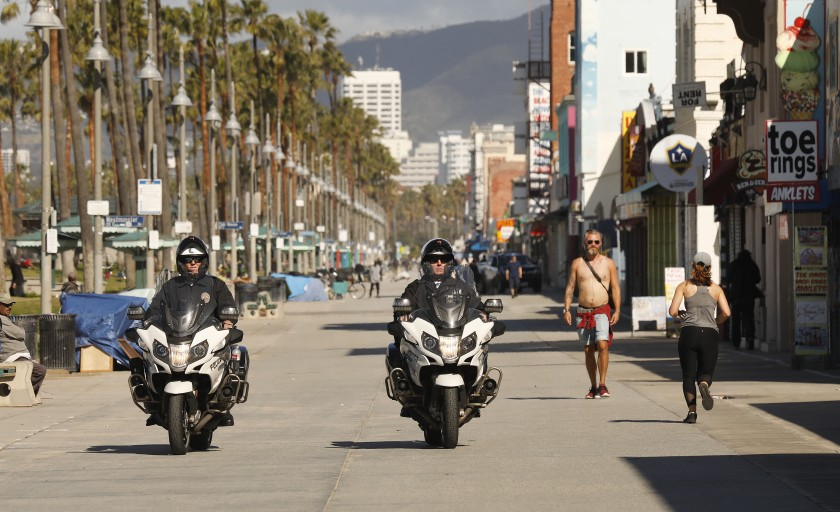 On March 23, 2020, amid mass closures over the COVID-19 outbreak, LAPD officers patrol a near-empty Venice boardwalk. (Al Seib / Los Angeles Times)