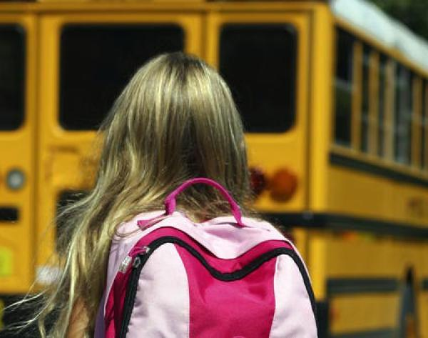 A child is seen near a school bus in this undated photo. (Los Angeles Times)