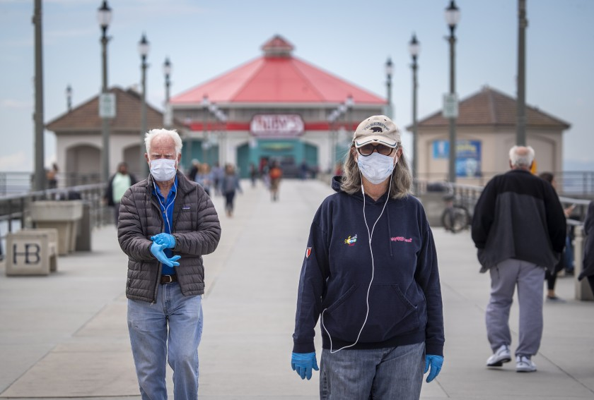 A couple in their 70s wear masks as they return from a walk on the Huntington Beach pier amid coronavirus restrictions. (Allen J. Schaben / Los Angeles Times)