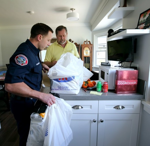Glendale Firefighter-Paramedic Spencer Hammond delivers groceries to 64-year-old Jim Rohrig in this undated photo. (Credit: Raul Roa/Glendale News-Press)