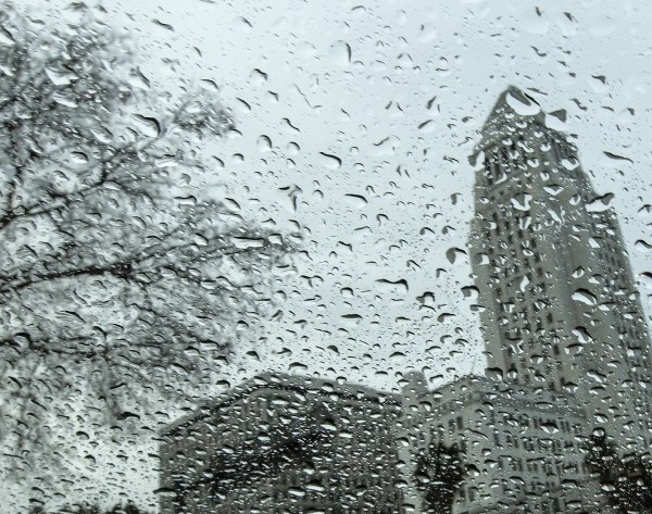 Los Angeles City Hall is pictured from behind glass covered in droplets on a rainy day in March 2020. (Credit: Los Angeles Times)