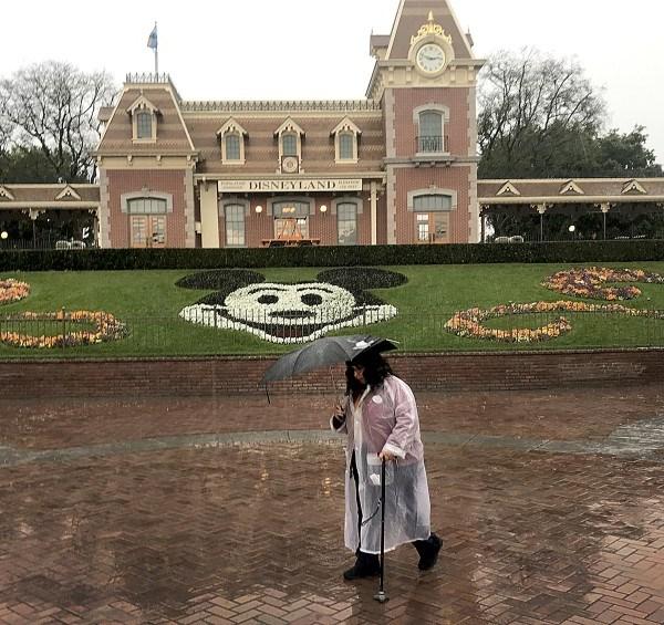 A Disneyland employee walks through the entrance to Disneyland during a rain shower in Anaheim on Thursday.(Allen J. Schaben / Los Angeles Times)