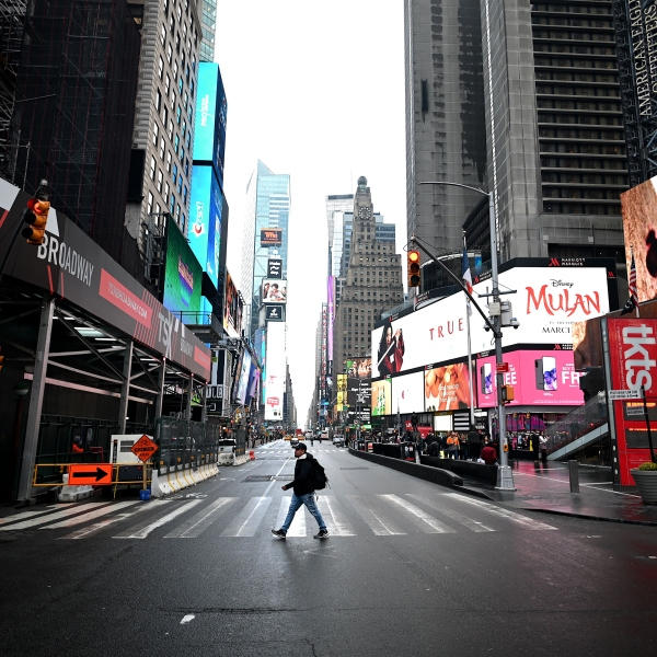 A tourist crosses the 7th Avenue at Times Square on March 13, 2020 in New York City. (Johannes Eisele/AFP/Getty Images)