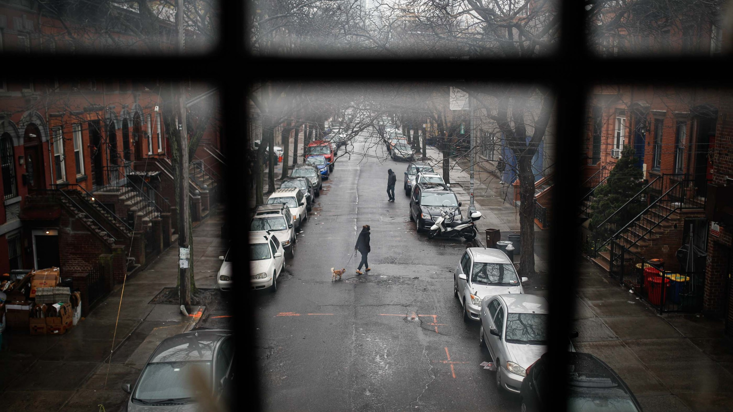 A pedestrian walks their dog through a quiet street, Tuesday, March 17, 2020, in the Brooklyn borough of New York. (AP Photo/John Minchillo)