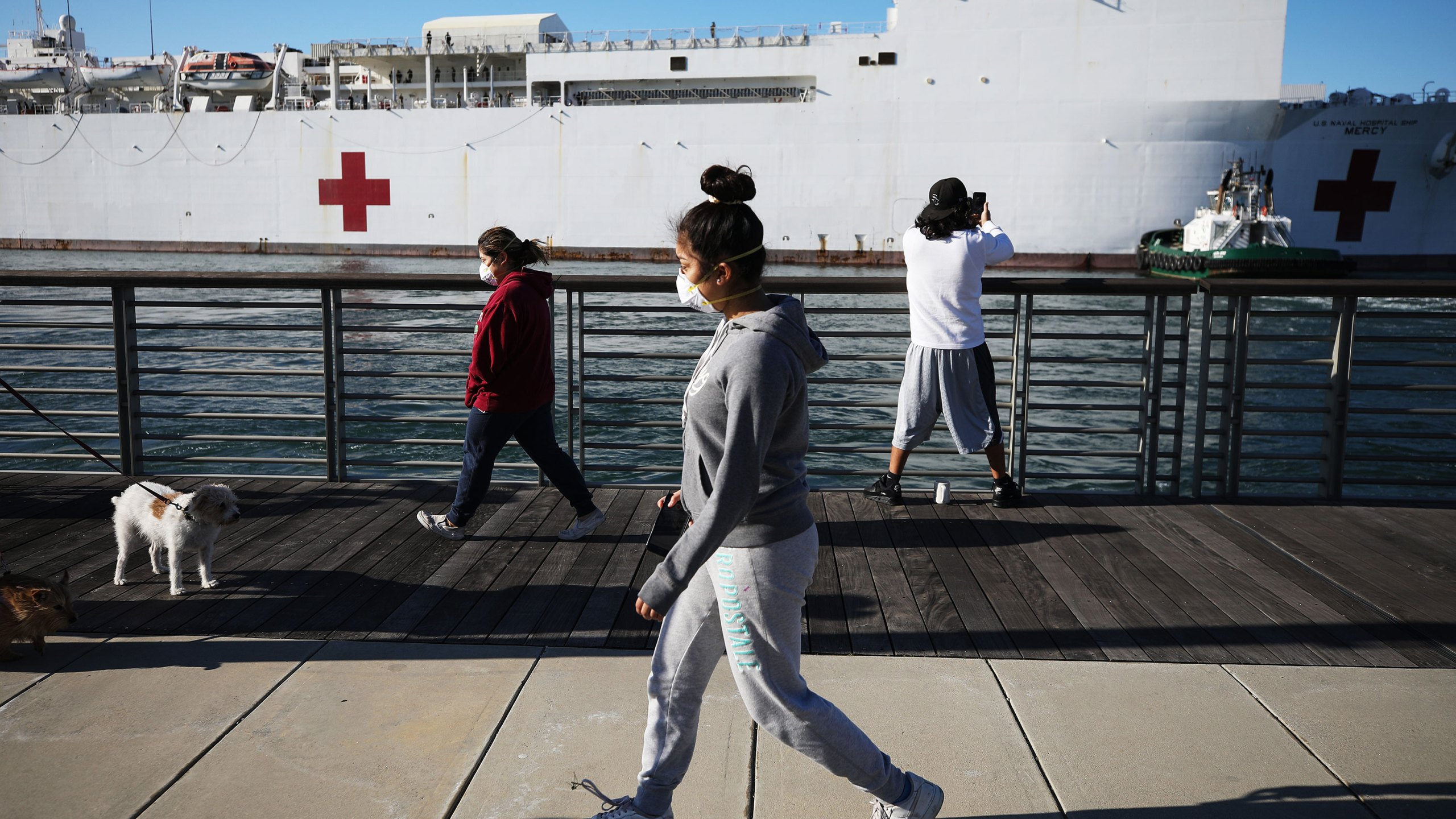 People wearing face masks walk near the USNS Mercy Navy hospital ship after it arrived in the Port of Los Angeles to assist with the coronavirus pandemic on March 27, 2020 in San Pedro. (Mario Tama/Getty Images)