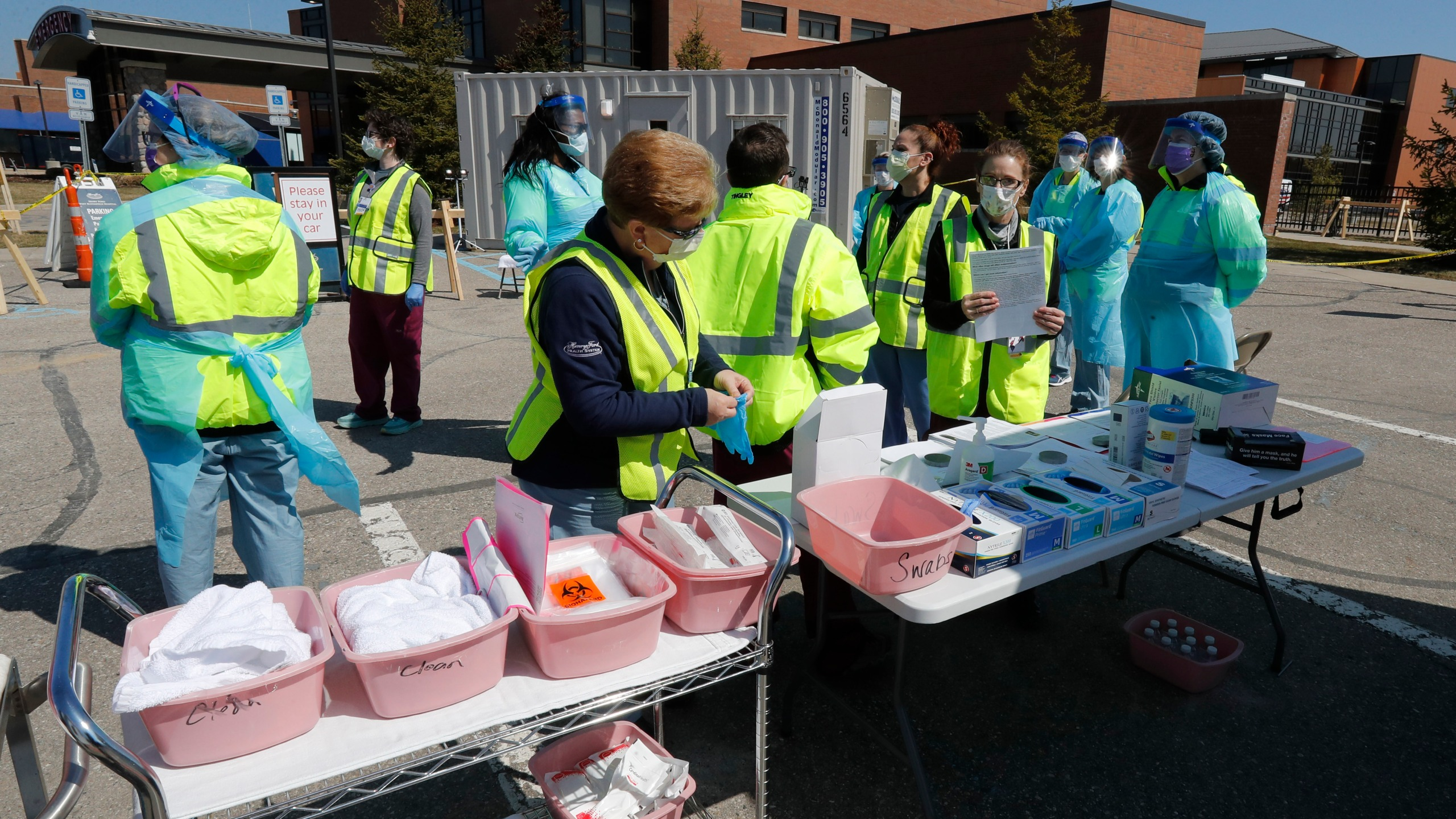Healthcare workers prepare their supplies at a COVID-19 drive-thru testing site at Henry Ford West Bloomfield Hospital, Wednesday, March 25, 2020, in West Bloomfield, Mich. (AP Photo/Carlos Osorio)