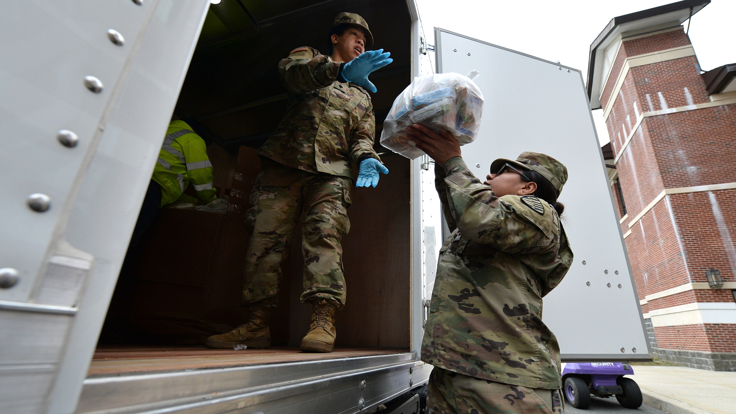 Army National Guard Specialists Arline (l) and Avila wear protective rubber gloves as they load bags of food for distribution from New Rochelle High School as part of New York State Gov. Andrew Cuomo deplyoment of the National Guard in the Westchester County town of New Rochelle in the coronavirus containment zone, New Rochelle, NY, March 12, 2020. (Anthony Behar/Sipa USA).