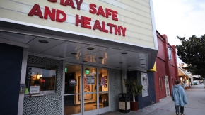 A pedestrian walks past a shuttered movie theater, with the message 'Stay Safe and Healthy' displayed on the marquee, on March 19, 2020, in Los Angeles. (Mario Tama/Getty Images)
