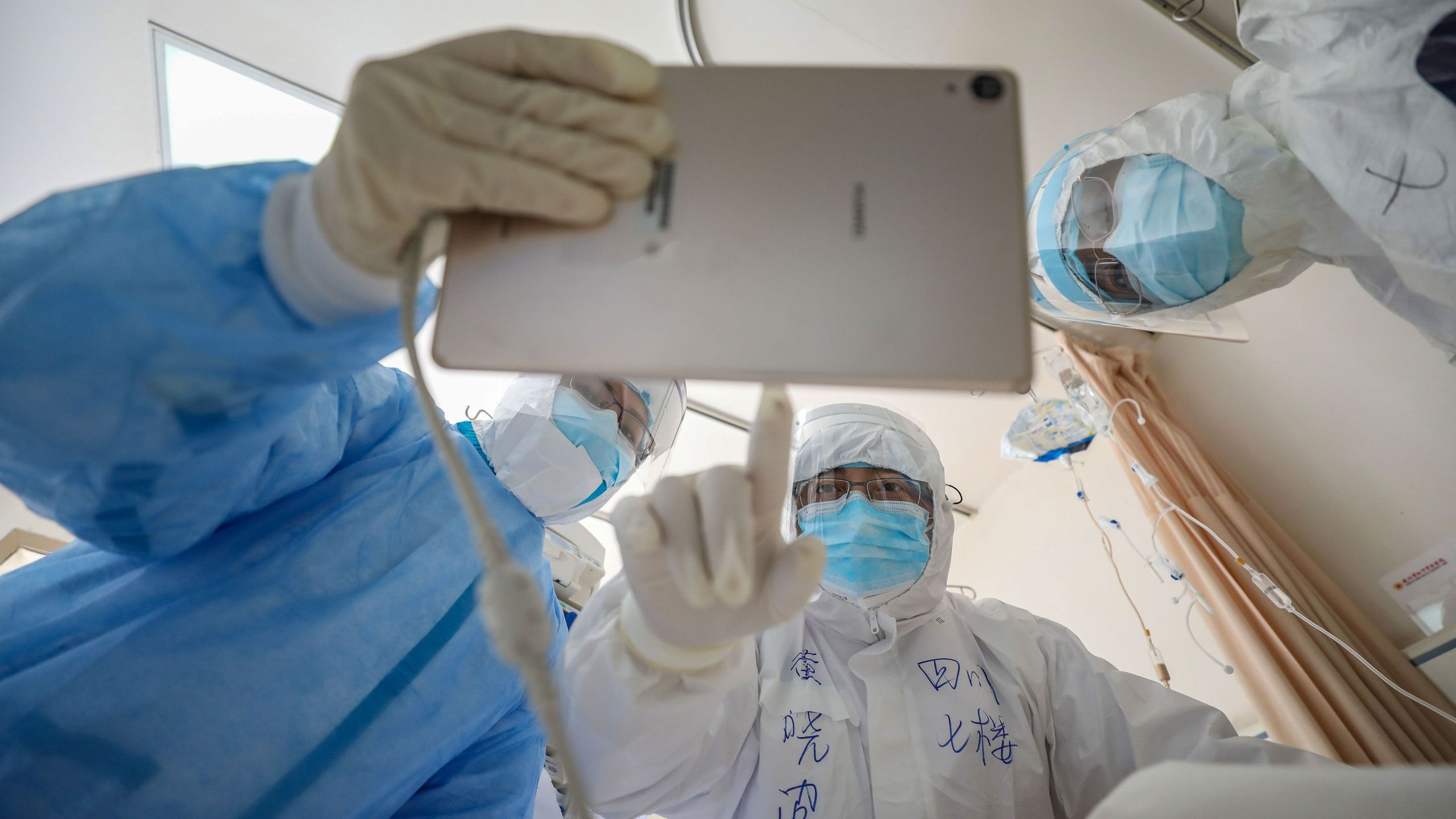 This photo taken on February 16, 2020 shows a doctor looking at an image as he checks a patient who is infected by the COVID-19 coronavirus at the Wuhan Red Cross Hospital in Wuhan in China's central Hubei province. (STR/AFP via Getty Images)