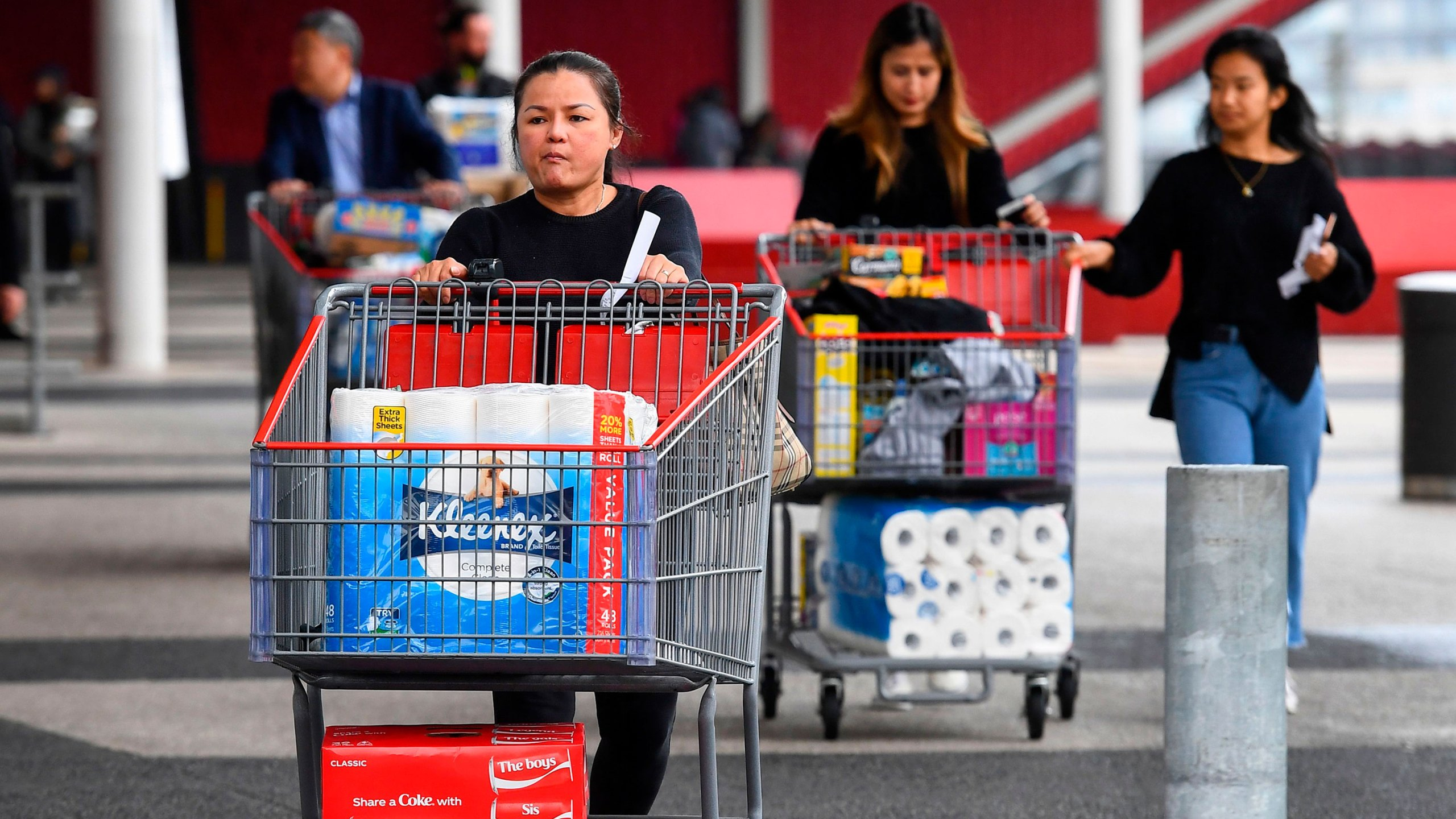 People leave a Costco warehouse with rolls of toilet paper amongst their groceries in Melbourne on March 5, 2020. (William West/AFP/Getty Images via CNN Wire)