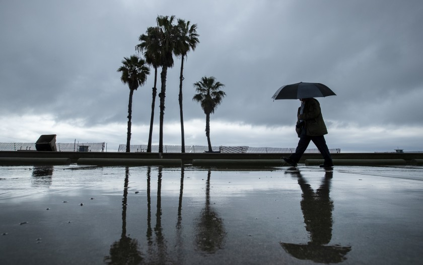 A pedestrian with an umbrella walks along the beach path in Santa Monica on Tuesday.(Brian van der Brug / Los Angeles Times)