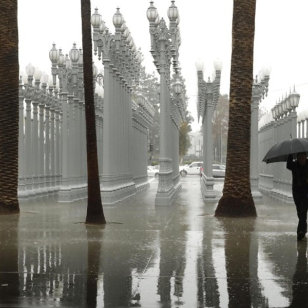 "A visitor to the Los Angeles County Museum of Art makes his way through the rain and walks by Chris Burden's sculpture ""Urban Light"" during an atmospheric river storm in February 2019. The first atmospheric river of 2020 will make its way to L.A. next week.(Genaro Molina / Los Angeles Times)"