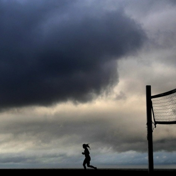 A woman runs on the sand in Redondo Beach beneath cloudy skies on Tuesday morning.(Christina House / Los Angeles Times)