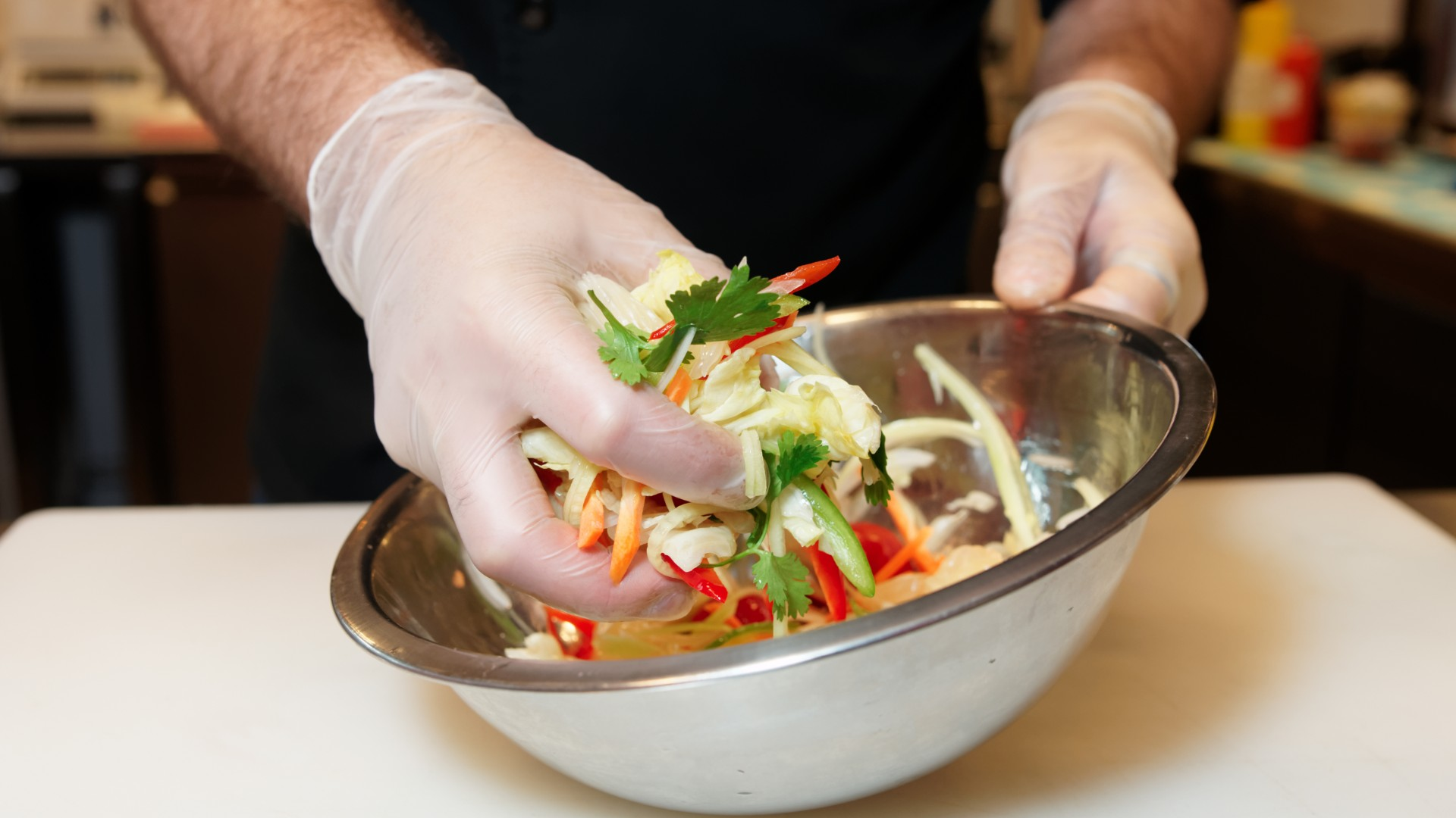 A worker wearing gloves mixes a salad in this file photo. (Getty images)