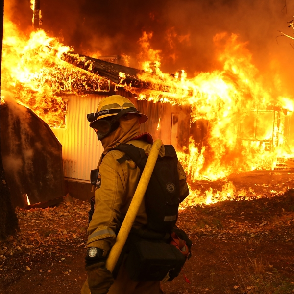 A Cal Fire firefighter is seen outside a burning home as the Camp Fire moves through the area on Nov. 9, 2018, in Magalia, California. (Justin Sullivan/Getty Images)