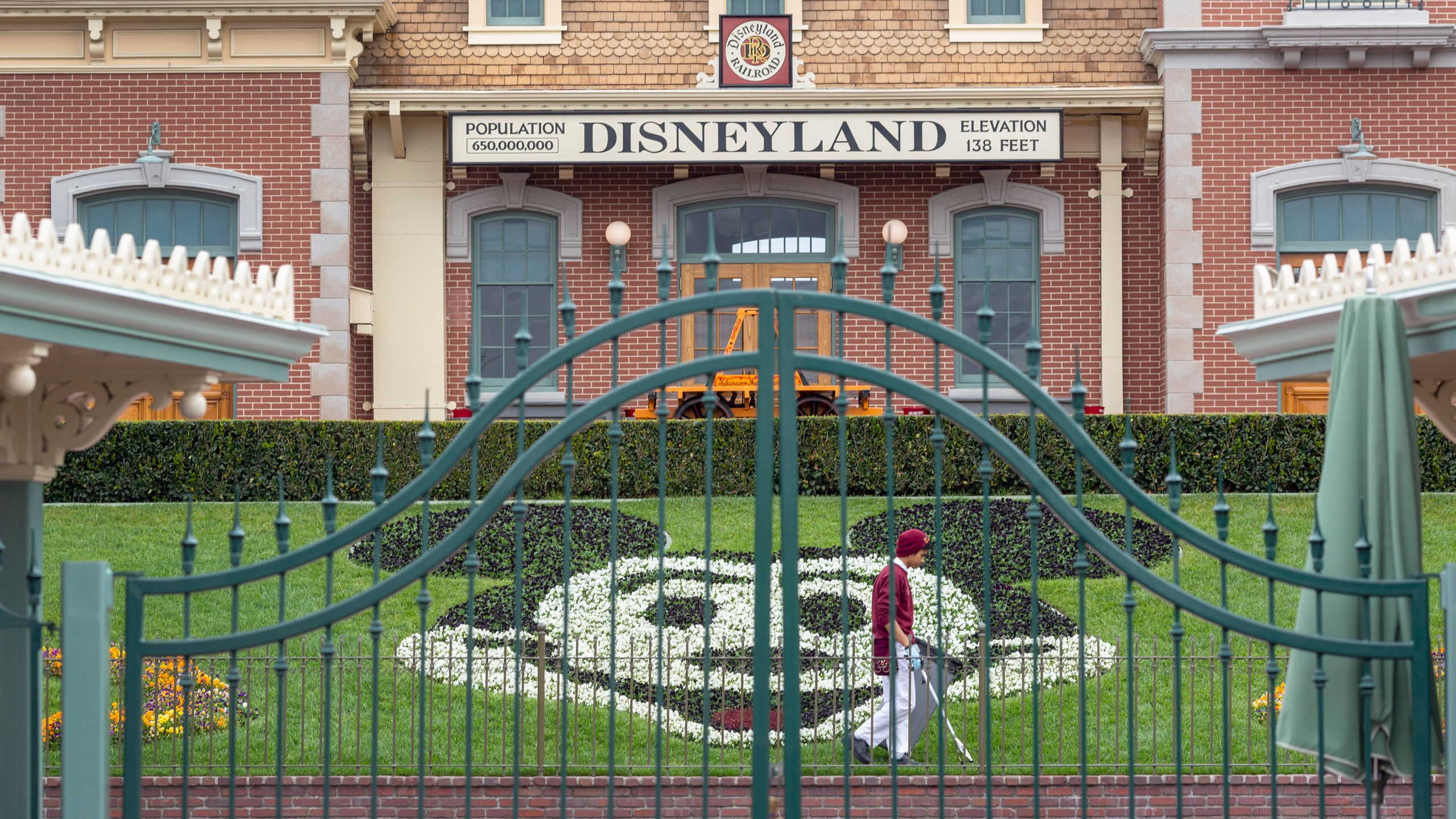 An employee cleans the grounds behind the closed gates of Disneyland Park on the first day of the closure of Disneyland and Disney California Adventure theme parks as fear of the spread of coronavirus continue, in Anaheim on March 14, 2020. (DAVID MCNEW/AFP via Getty Images)