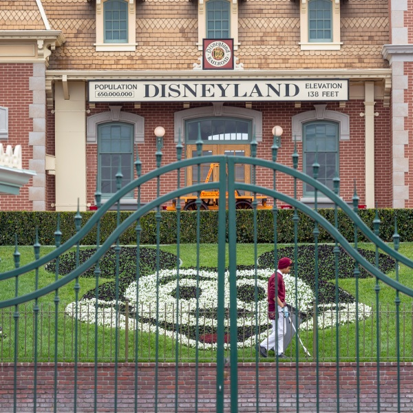 An employee cleans the grounds behind the closed gates of Disneyland in Anaheim on the first day of the resort's closure amid fear of the spread of coronavirus, March 14, 2020. (David McNew / AFP / Getty Images)