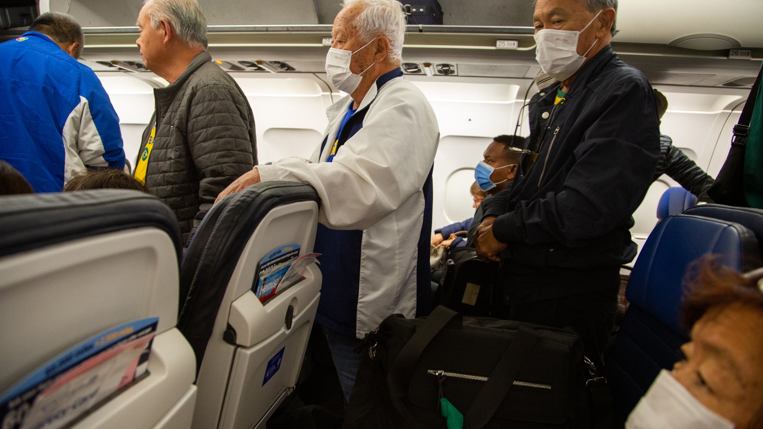 Passengers wear protective face masks in a airplane after arrival in Houston International Airport on March 14, 2020 in Houston, Texas (Carol Coelho/Getty Images)